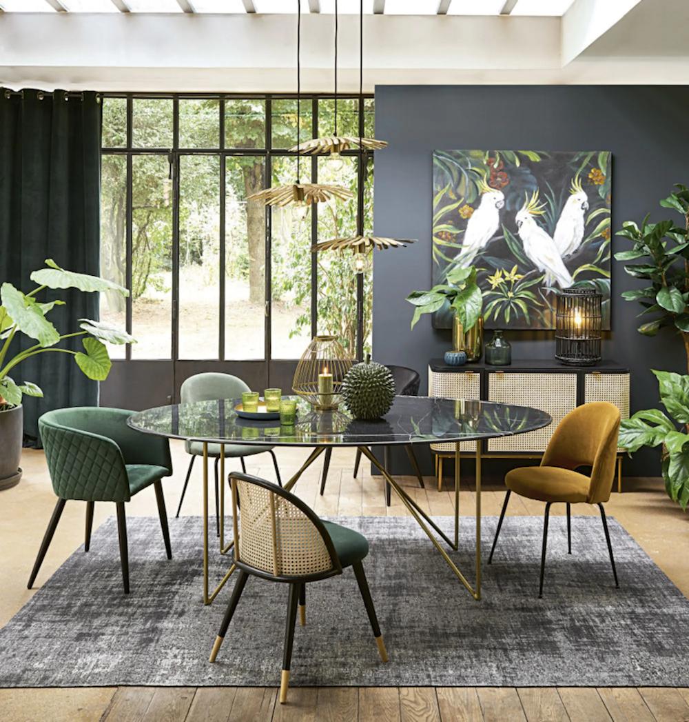 salle à manger urban jungle table ronde suspension en laiton chaises dépareillées tapis gris
