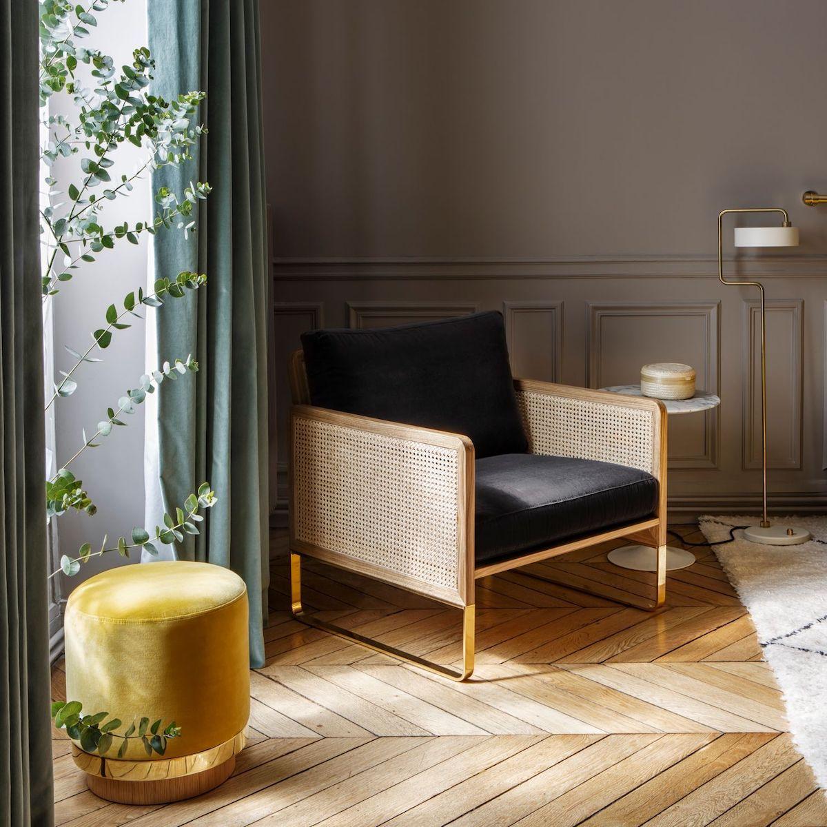 salon élégant parquet chevron bois pouf jaune velours laiton fauteuil noir cannage