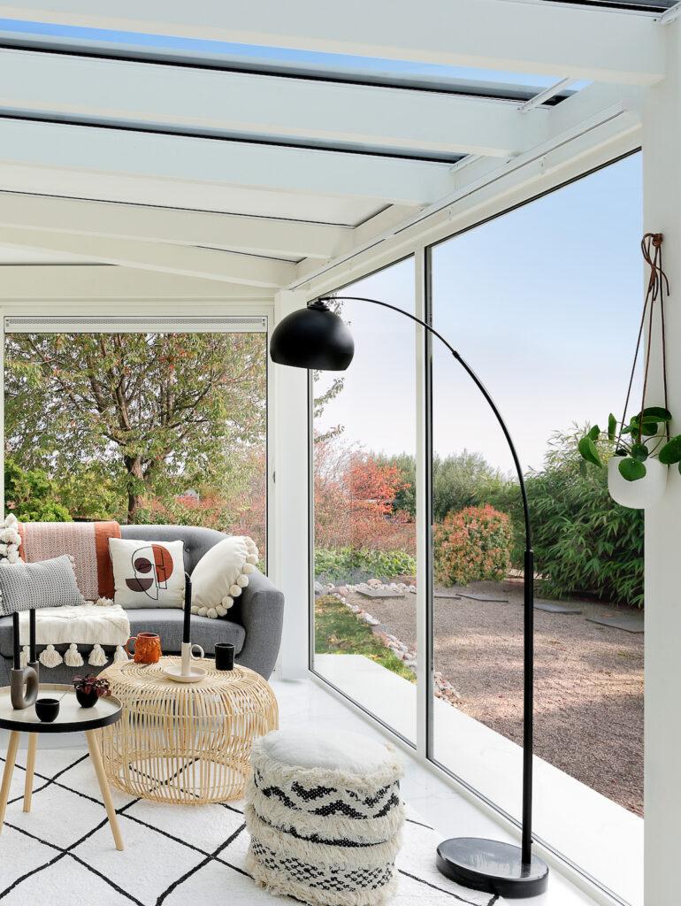 salon lumineux veranda baie vitrée accessoire rotin tapis berbère noir et blanc