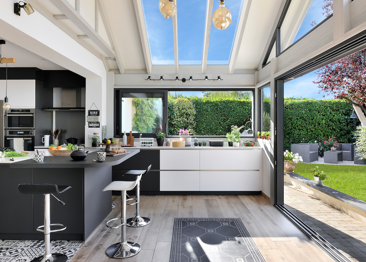veranda extension maison toit ouvert cuisine américaine noir sol parquet