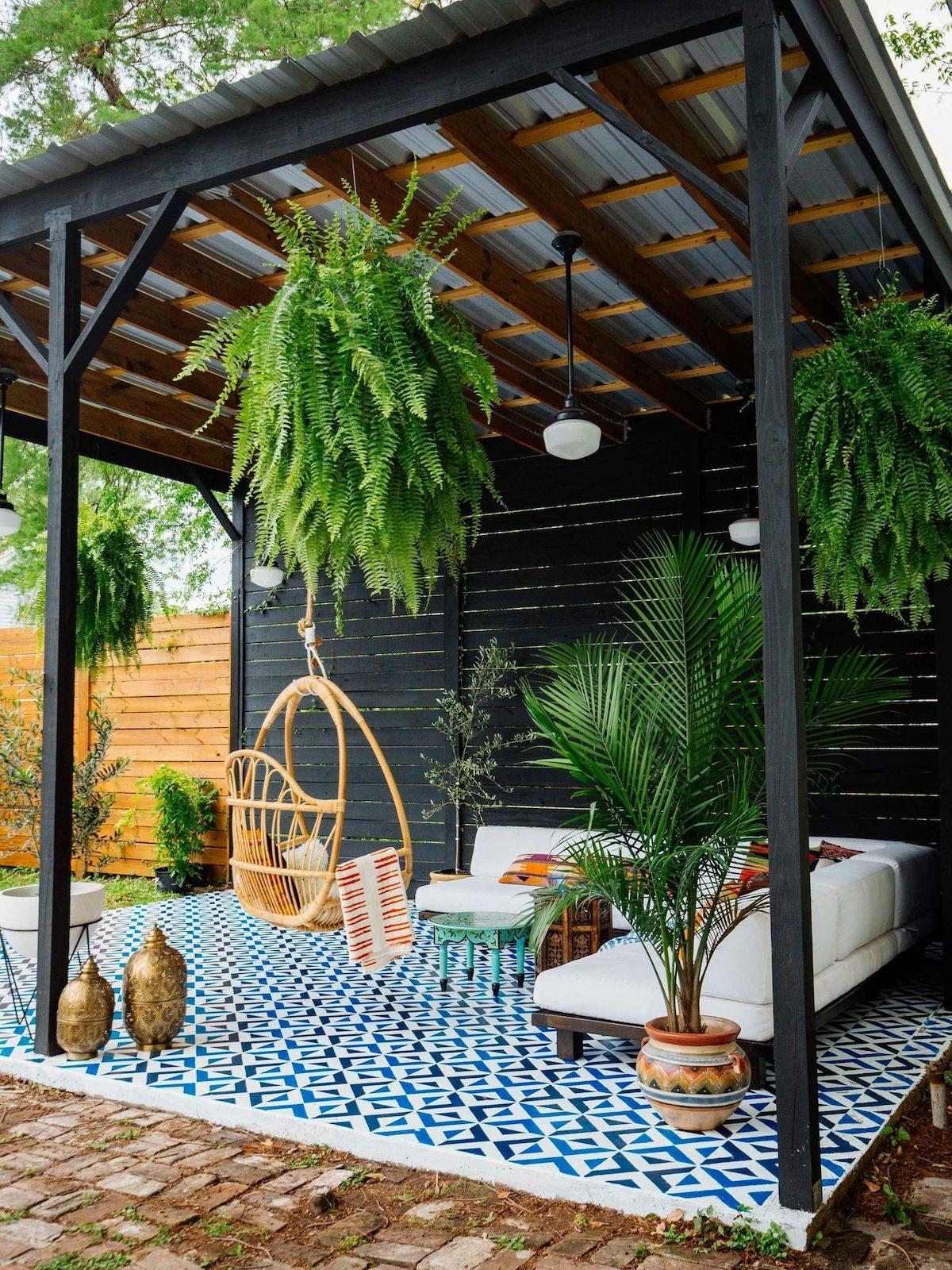 terrasse noire pergola sol bleu canapé blanc plantes vertes