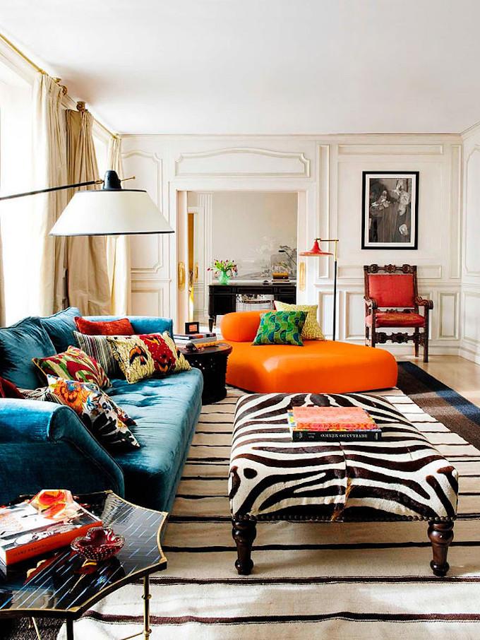 salon lumineux style éclectique canapé velours bleu canard fauteuil orange tapis rayé blanc noir